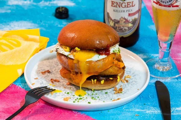 A Snail-shaped, Coiled Sausage Topped with a Fried Egg and Served in a Bun