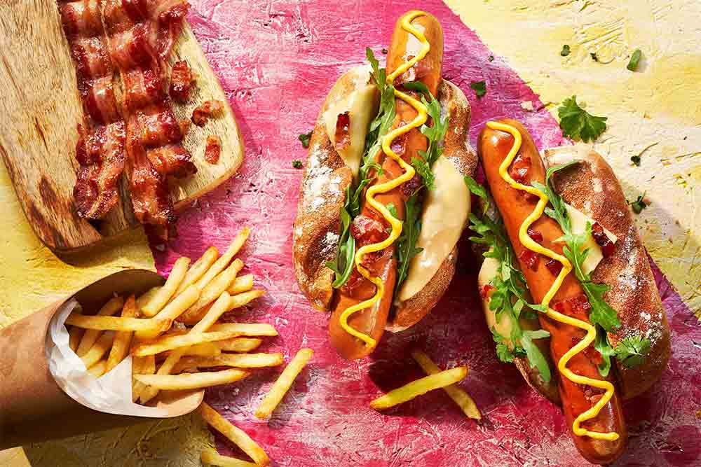 2 Hot Dogs in a bun with chips and bacon aside on a coloured wooden board
