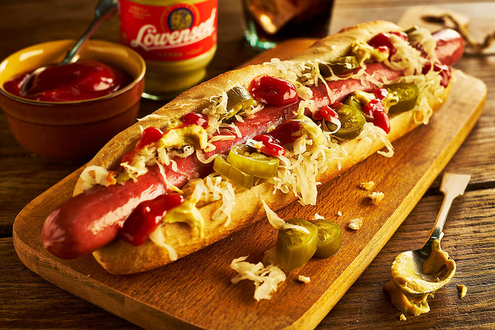 Hot Dog in a roll on a wooden board nicely decorated