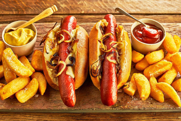 Two Vienna Beef sausages in roll with sauce, chips and sauce on the side.
