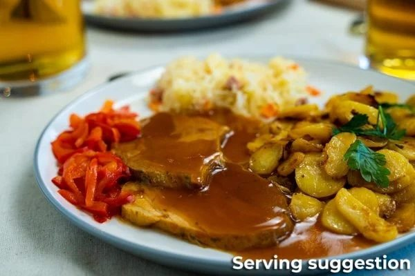 German Roast Pork in Gravy Served with Potatoes and Peppers