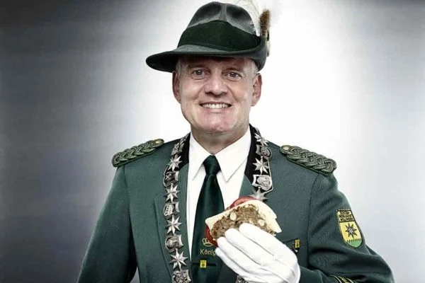 Man in traditional German dress holding a sandwich made from Traubennussbrot Grape and Nut Bread
