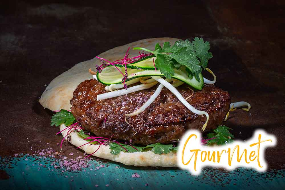 A grilled Wagyu beef patty on chiabatta, decorated with herbs and veggies on a colourful background